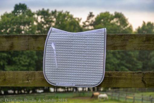 Horze Duchess dressage saddle pad in white hanging over fence