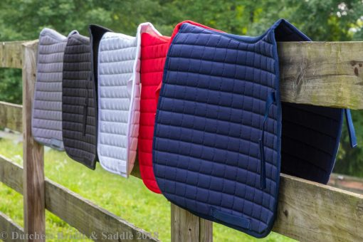 Horze Bristol AP saddle pads in fall 2018 colors hanging over fence post